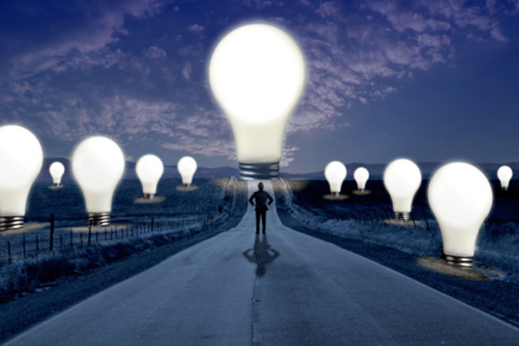 Man standing on road surrounded by oversized lightbulbs